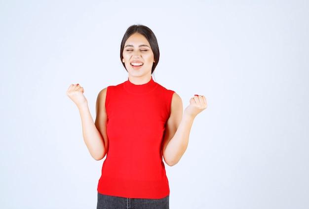 Dziewczyna w czerwonej koszuli pokazano jej mięśnie ramion i pięści.