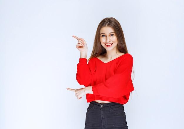 Dziewczyna w czerwonej koszuli pokazując coś po lewej stronie.