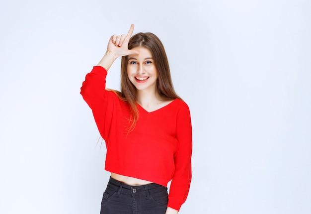 Dziewczyna w czerwonej koszuli pokazując znak przegranego na czole.