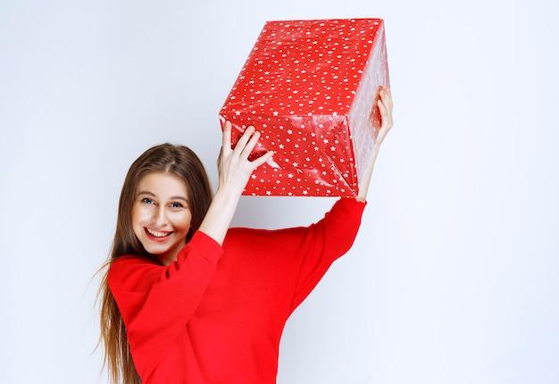 Dziewczyna w czerwonej koszuli potrząsa pudełkiem prezentowym owiniętym czerwoną wstążką
