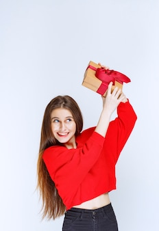Dziewczyna w czerwonej koszuli potrząsając pudełkiem owiniętym czerwoną wstążką, aby odgadnąć, co jest w środku.