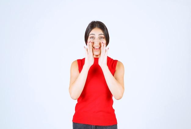 Dziewczyna w czerwonej koszuli pozdrowienie lub zaproszenie kogoś.