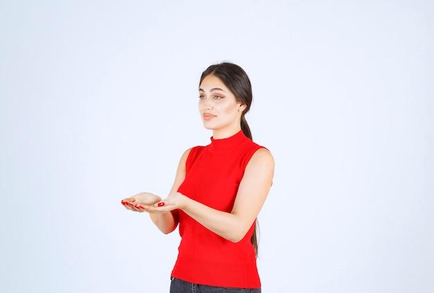 Dziewczyna w czerwonej koszuli prezentując i pokazując coś w dłoni.