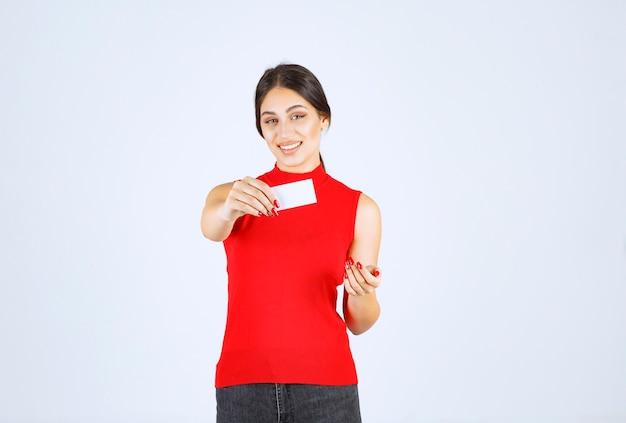 Dziewczyna w czerwonej koszuli prezentuje swoją wizytówkę.