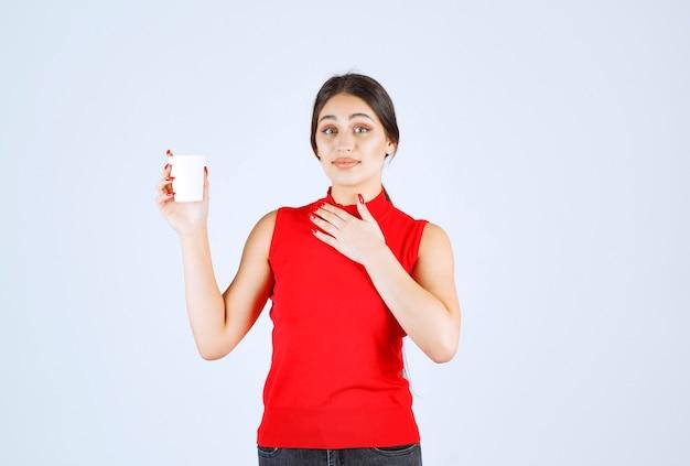 Dziewczyna w czerwonej koszuli trzyma białą filiżankę kawy i wskazuje na siebie.