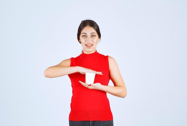 Dziewczyna w czerwonej koszuli trzyma białą filiżankę kawy między rękami.
