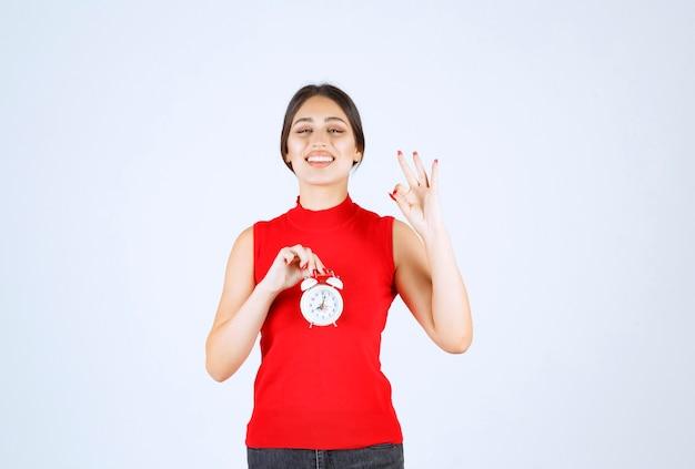 Dziewczyna w czerwonej koszuli trzyma budzik i cieszy się produktem.