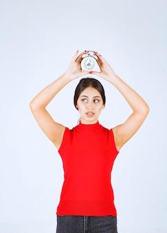 Dziewczyna w czerwonej koszuli trzyma budzik nad głową.