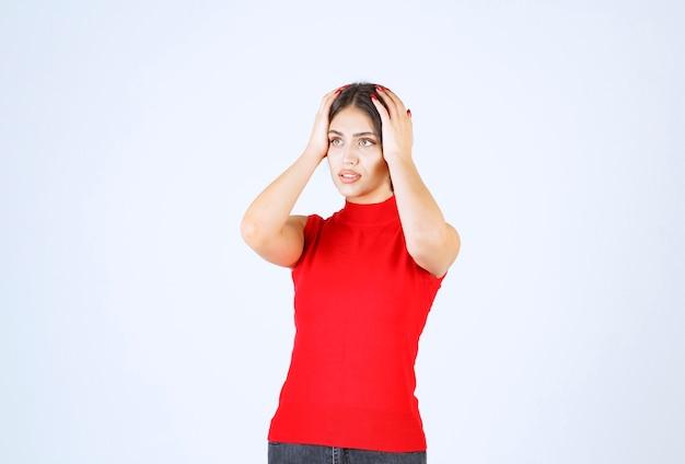 Dziewczyna w czerwonej koszuli trzyma głowę rękami, bo boli ją głowa.