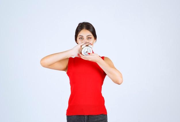 Dziewczyna w czerwonej koszuli trzyma i promuje budzik.
