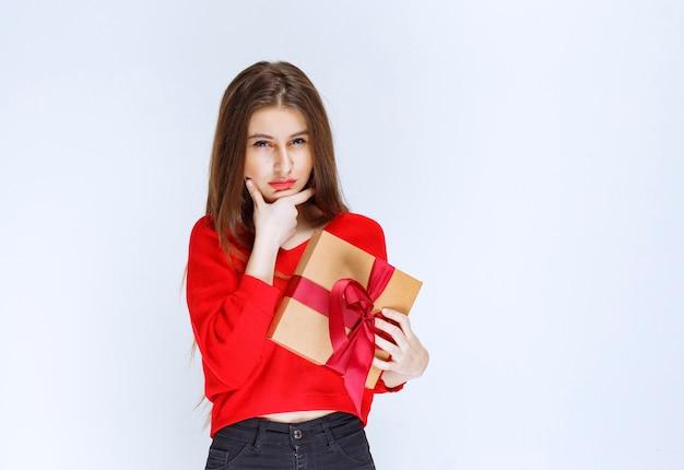 Dziewczyna w czerwonej koszuli trzyma kartonowe pudełko owinięte czerwoną wstążką i wygląda na zdezorientowaną i zamyśloną.