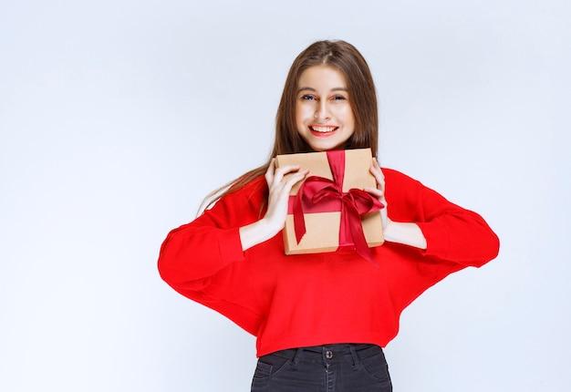 Dziewczyna w czerwonej koszuli trzyma kartonowe pudełko owinięte czerwoną wstążką.