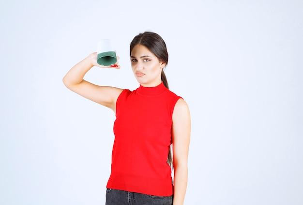 Dziewczyna w czerwonej koszuli trzyma kubek do góry nogami.