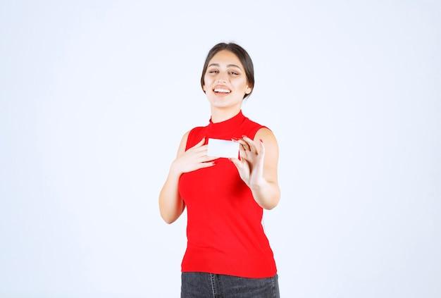Dziewczyna w czerwonej koszuli trzyma wizytówkę i prezentuje się.