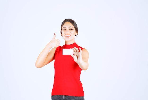 Dziewczyna w czerwonej koszuli trzyma wizytówkę i wygląda na zadowoloną.