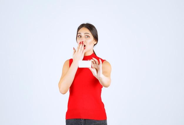 Dziewczyna w czerwonej koszuli trzyma wizytówkę i wygląda na zdziwioną.