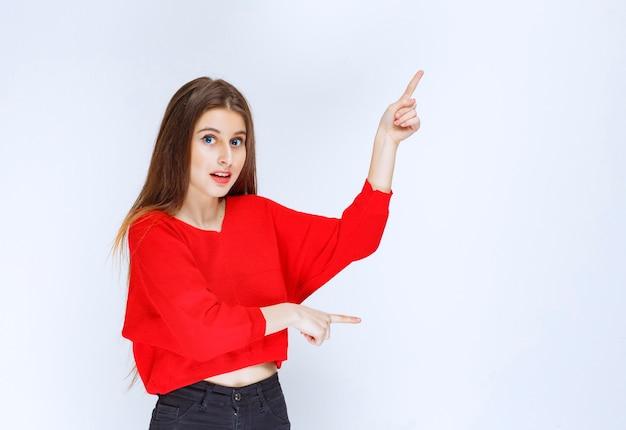 Dziewczyna W Czerwonej Koszuli, Wskazując Do Góry. Darmowe Zdjęcia