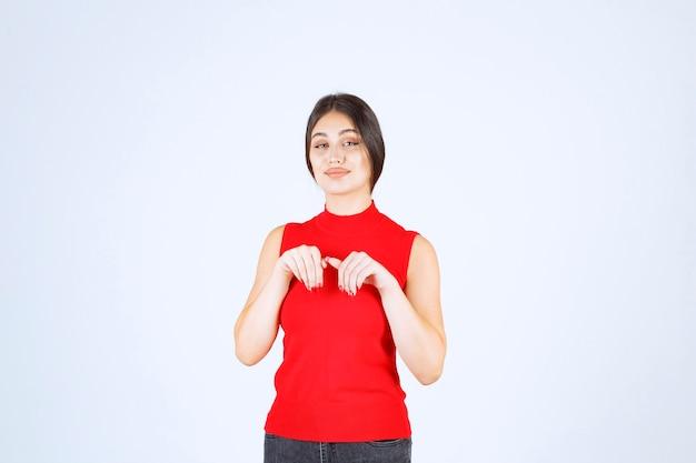 Dziewczyna w czerwonej koszuli, wskazując gdzieś poniżej.