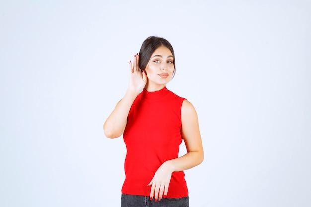 Dziewczyna w czerwonej koszuli wskazując jej ucho, aby dobrze słyszeć.