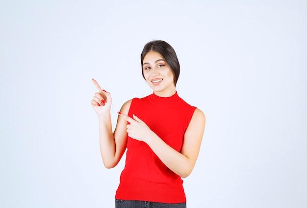 Dziewczyna w czerwonej koszuli, wskazując na coś po lewej stronie.