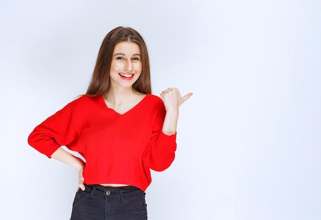 Dziewczyna w czerwonej koszuli, wskazując na coś za.