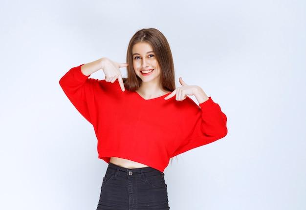 Dziewczyna w czerwonej koszuli, wskazując na siebie.