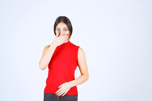 Dziewczyna w czerwonej koszuli, wskazując na usta i prosząca o ciszę.