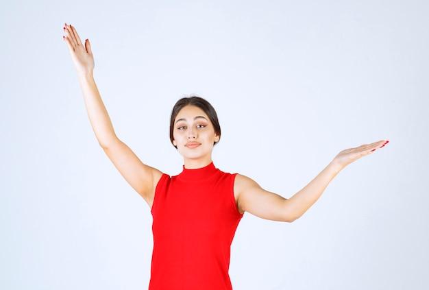 Dziewczyna w czerwonej koszuli, wskazując po obu stronach.
