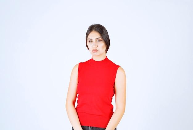 Dziewczyna w czerwonej koszuli wygląda na smutną i rozczarowaną.