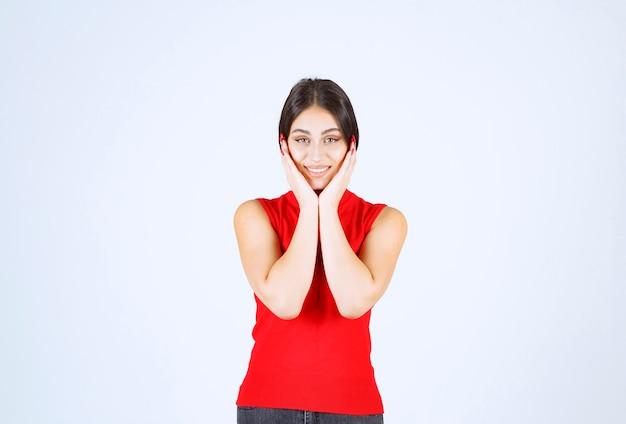 Dziewczyna w czerwonej koszuli wygląda na zaskoczoną czymś nieoczekiwanym.