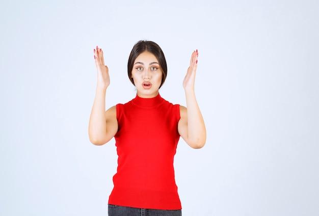 Dziewczyna w czerwonej koszuli wygląda na zestresowaną i zdenerwowaną.