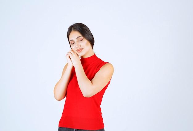 Dziewczyna w czerwonej koszuli wygląda na zmęczoną i senną.