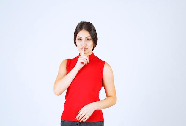 Dziewczyna w czerwonej koszuli z prośbą o ciszę.