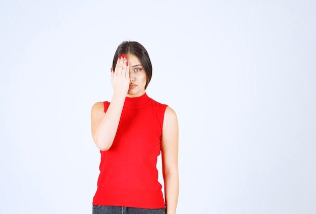 Dziewczyna w czerwonej koszuli zakrywając ręką część twarzy.