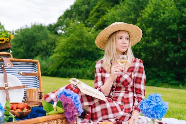 Dziewczyna w czerwonej kraciastej sukience i kapeluszu siedzi na białej dzianiny koc piknikowy, czytanie książki i picie wina. letni piknik w słoneczny dzień z chlebem, owocami, bukietem kwiatów hortensji. selektywna ostrość.