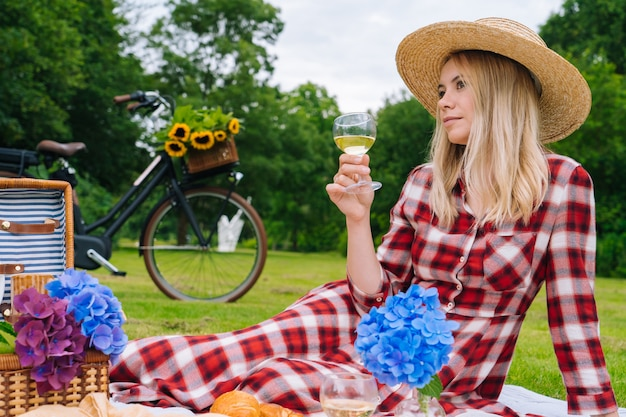 Dziewczyna w czerwonej kraciastej sukience i kapeluszu siedzi na dzianiny koc piknikowy, czytanie książki i picie wina.