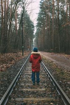 Dziewczyna w czerwonej kurtce i niebieskiej czapce spacerująca wzdłuż torów kolejowych w jesiennym lesie w berlinie