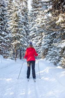 Dziewczyna w czerwonej kurtce jedzie na nartach w zaśnieżonym lesie zimą. widok z tyłu.