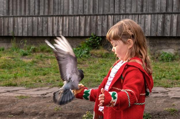 Dziewczyna w czerwonej kurtce karmi gołąbka z rąk chleba w parku