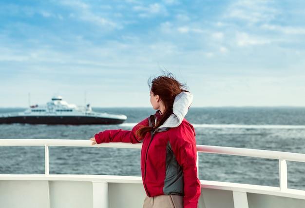 Dziewczyna w czerwonej kurtce na promie patrzy w kierunku morza, gdzie pływa liniowiec