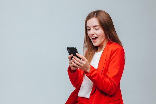 Dziewczyna w czerwonej kurtce pisze wiadomość przez telefon