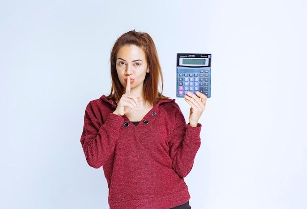 Dziewczyna w czerwonej kurtce przeliczająca coś na niebieskim kalkulatorze, pokazująca wynik i prosząca o ciszę.