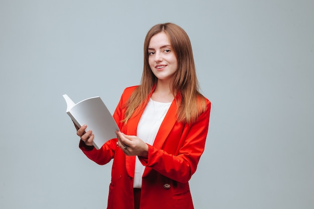 Dziewczyna w czerwonej kurtce trzyma pusty zeszyt