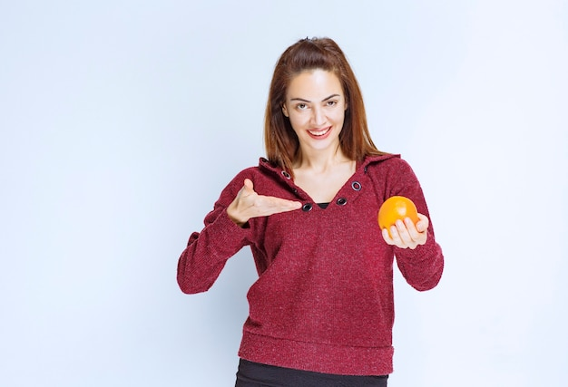 Dziewczyna w czerwonej kurtce trzymająca pomarańczę