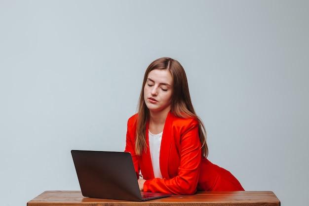 Dziewczyna w czerwonej kurtce z laptopem przy jasnym tle stołu