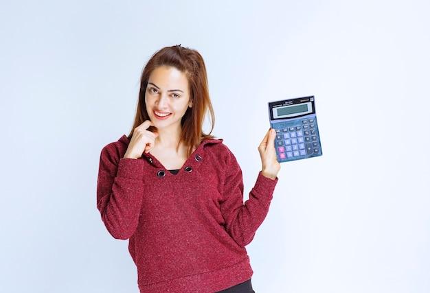 Dziewczyna w czerwonej marynarce oblicza coś na niebieskim kalkulatorze i pokazuje wynik końcowy.