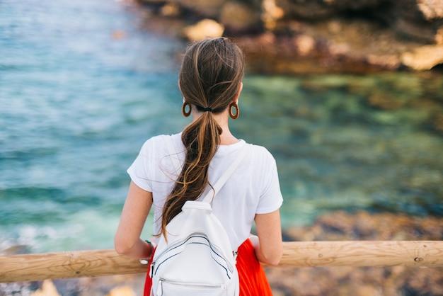Dziewczyna w czerwonej sukience eskortuje zachód słońca nad morze. poziomy baner fotograficzny do projektowania nagłówka witryny z miejscem na kopię tekstu. widok kobiety z tyłu.