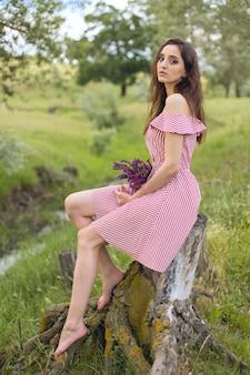 Dziewczyna w czerwonej sukience na naturze latem, portret pięknej dziewczyny latem w lesie