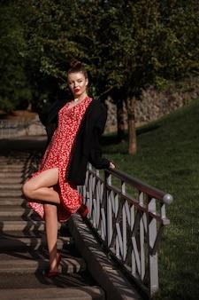 Dziewczyna w czerwonej sukience na spacerze w parku w lecie.