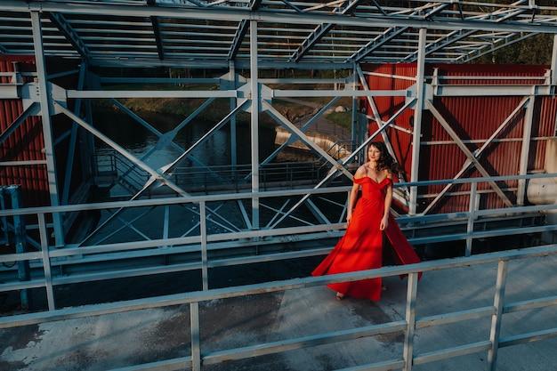 Dziewczyna w czerwonej sukience na tamie w pobliżu rzeki o zachodzie słońca.